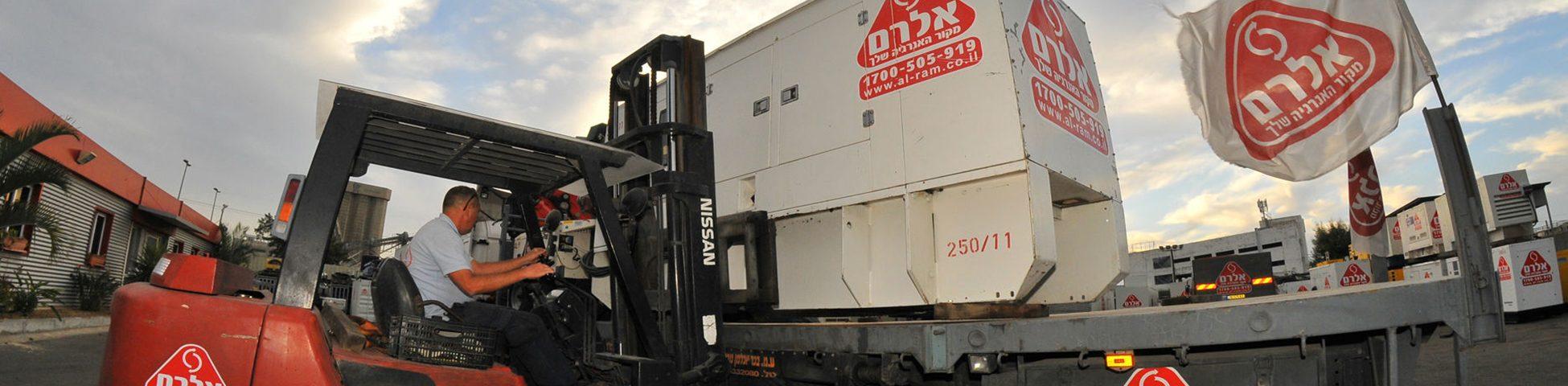 עובד חברת אלרם מניח באמצעות מלגזה גנרטור על גבי מרכב משאית